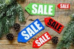 De verkoop van de winter De verkoop etiketteert dichtbij nette takken op houten hoogste mening als achtergrond Royalty-vrije Stock Foto