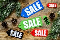 De verkoop van de winter De verkoop etiketteert dichtbij nette takken op houten hoogste mening als achtergrond Stock Foto