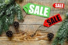De verkoop van de winter De verkoop etiketteert dichtbij nette takken op houten hoogste mening als achtergrond copyspace Royalty-vrije Stock Afbeeldingen