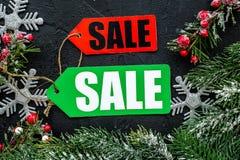 De verkoop van de winter De verkoop etiketteert dichtbij nette takken op zwarte hoogste mening als achtergrond Stock Fotografie