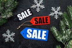 De verkoop van de winter De verkoop etiketteert dichtbij nette takken op zwarte hoogste mening als achtergrond Stock Foto's