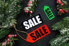 De verkoop van de winter De verkoop etiketteert dichtbij nette takken op zwarte hoogste mening als achtergrond Royalty-vrije Stock Afbeeldingen