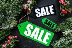 De verkoop van de winter De verkoop etiketteert dichtbij nette takken op zwarte hoogste mening als achtergrond Royalty-vrije Stock Afbeelding