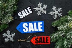 De verkoop van de winter De verkoop etiketteert dichtbij nette takken op zwarte hoogste mening als achtergrond Stock Foto