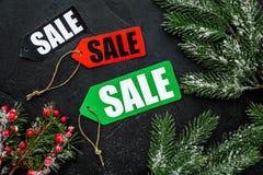 De verkoop van de winter De verkoop etiketteert dichtbij nette takken op zwarte hoogste mening als achtergrond Stock Afbeeldingen