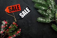 De verkoop van de winter De verkoop etiketteert dichtbij nette takken op zwarte hoogste mening als achtergrond copyspace Royalty-vrije Stock Afbeelding