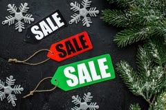 De verkoop van de winter Word de verkoop op colorfil etiketteert dichtbij Kerstmisspeelgoed en nette tak op zwarte hoogste mening Stock Fotografie