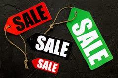 De verkoop van de winter Word verkoop op kleurrijke etiketten op zwarte steen hoogste mening als achtergrond Stock Foto