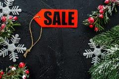 De verkoop van de winter Word verkoop op rood etiket dichtbij Kerstmisspeelgoed en nette tak op zwarte hoogste mening als achterg Stock Afbeeldingen