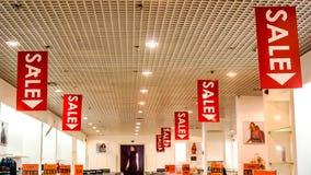 De verkoopaffiches bij manier kleedt zich shopfront Stock Foto