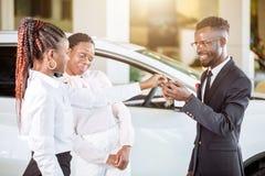 De verkoopsituatie in het autohandel drijven, jong Afrikaans paar krijgt de sleutel voor nieuwe auto royalty-vrije stock foto