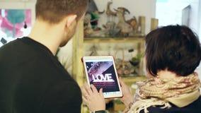 De verkoopster in een bloemwinkel die klanten mogelijke opties van boeketten op de tablet tonen stock video