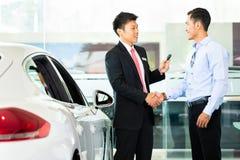 De verkopende auto van de autoverkoper aan klant Stock Foto's