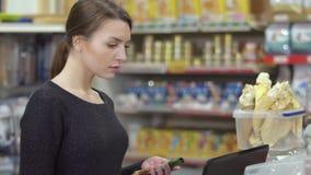 De verkoper controleert de productbeschikbaarheid in gegevensbestand in dierenwinkel stock video