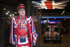 De verkoper draagt eenvormig symboliserend de Engelse vlag bij de ingang van de opslag Koele Britannia Royalty-vrije Stock Fotografie