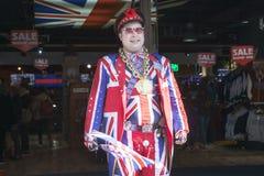 De verkoper draagt eenvormige het symboliseren Engelse vlag bij ingang van winkel Koele Britannia In auto als achtergrond die in  Stock Fotografie