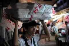 De verkoper draagt Voedsel op Hoofd Stock Fotografie