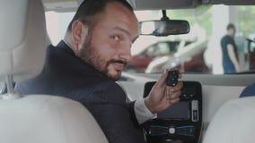 De verkoper geeft een sleutelszakenman van een nieuwe auto stock video