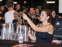 De verkoper giet bier in een glas aan de koper in een straatwinkel bij de viering van de dag van de stad van Nahariya in Israël Stock Foto