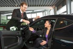 De verkoper in het autohandel drijven verkoopt auto aan klant stock fotografie