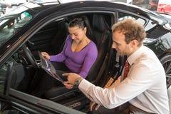 De verkoper in het autohandel drijven verkoopt auto aan klant stock foto