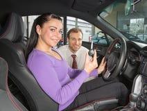 De verkoper in het autohandel drijven verkoopt auto aan klant royalty-vrije stock fotografie