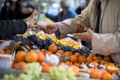 De verkoper keurt betaling bij een straatmarkt goed Stock Foto's
