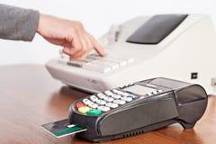 De verkoper maakt de berekening en neemt betaling door contant geldreg. Royalty-vrije Stock Afbeelding