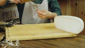 De verkoper overhandigt een stuk van kaas wordt ingepakt in document verpakking stock video