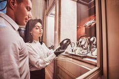 De verkoper toont de cliënt een exclusief horloge die van mensen zich naast open showcase bevinden stock afbeeldingen