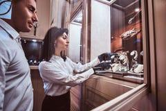 De verkoper toont de cliënt een exclusief horloge die van mensen zich naast open showcase bevinden royalty-vrije stock foto's