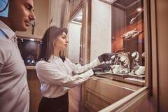 De verkoper toont de cliënt een exclusief horloge die van mensen zich naast open showcase bevinden stock foto