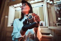 De verkoper toont een exclusief polshorloge van mensen van de nieuwe inzameling in de opslag van luxejuwelen stock afbeelding