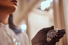 De verkoper toont een exclusief polshorloge van mensen van de nieuwe inzameling in de opslag van luxejuwelen royalty-vrije stock afbeelding