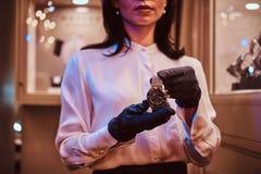 De verkoper toont een exclusief polshorloge van mensen van de nieuwe inzameling in de opslag van luxejuwelen stock foto's