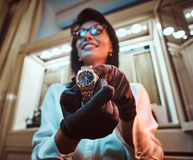 De verkoper toont een exclusief polshorloge van mensen van de nieuwe inzameling in de opslag van luxejuwelen stock foto