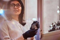 De verkoper toont een exclusief polshorloge van mensen van de nieuwe inzameling in de opslag van luxejuwelen royalty-vrije stock afbeeldingen