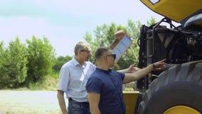 De verkoper toont tractor aan landbouwer stock videobeelden
