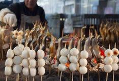 De verkoper van het straatvoedsel kookt yakitory en zoete rijstballen op de open brand royalty-vrije stock foto's