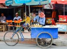 De verkoper van het straatvoedsel met zijn driewieler als voedselbox, in het stadscentrum, Phnom Penh, Kambodja 30 augustus, 2015 Stock Foto's