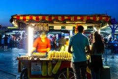 De verkoper van het straatvoedsel verkoopt maïskolven en geroosterde kastanjes op royalty-vrije stock foto's