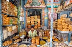 De verkoper van snoepjes wacht op kopers in een kleurrijke winkel met koekjes en snacks Stock Afbeelding