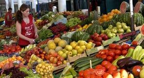 De verkoper verkoopt groenten bij de markt stock foto