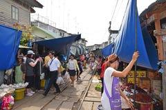 De verkopers houden hun boxen vanaf de komende trein bij Maeklong-Spoorwegmarkt Stock Foto's