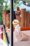 De verkopers` s hand van het venster rekt een wafeltje van zacht roomroomijs uit royalty-vrije stock foto's