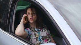 De verlagende dame in auto die aan de mens spreken die telefoon, luxe zekere vrouw met behulp van zit stock video