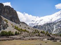 De verlaten bouw bij uitloper van berg met de sneeuwberg bij afstand Stock Fotografie