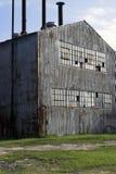De verlaten fabrieksbouw en schoorsteen Stock Foto's