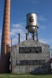 De verlaten fabrieksbouw met watertoren en schoorsteen Royalty-vrije Stock Afbeelding