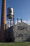 De verlaten fabrieksbouw met watertoren en schoorsteen Royalty-vrije Stock Foto's
